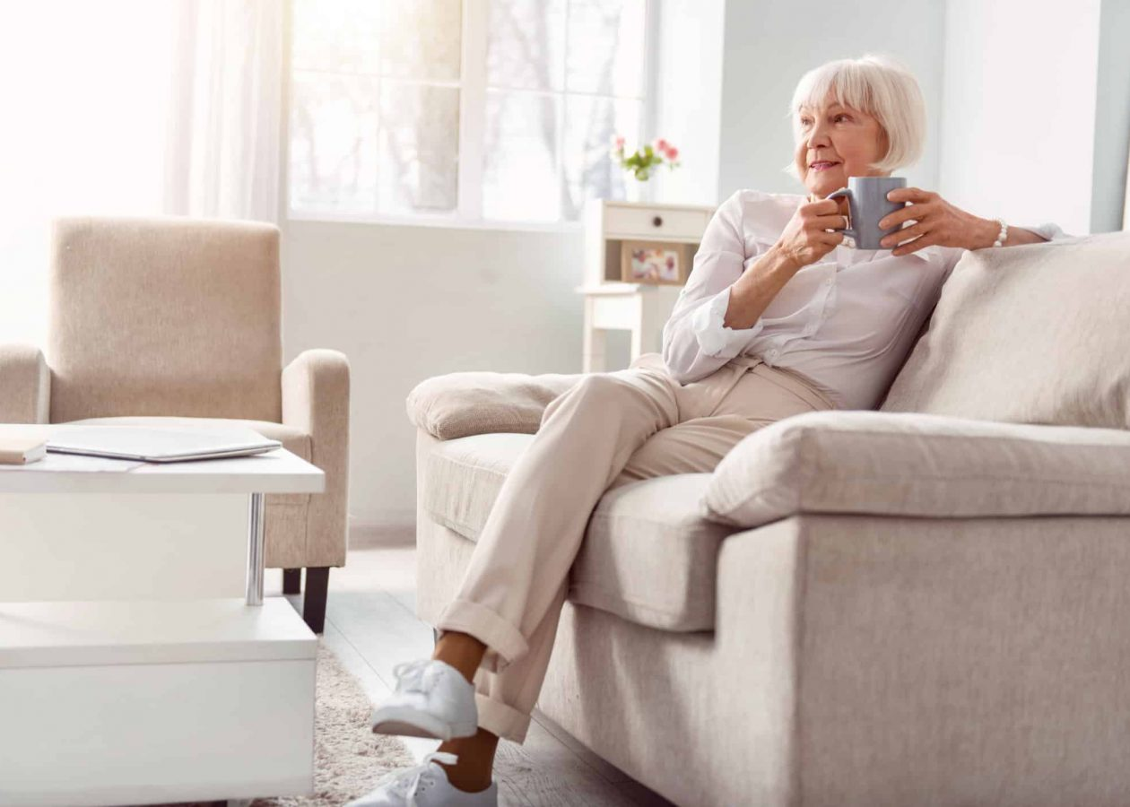 Relaxing in morning. Beautiful elderly woman sitting on the couch in her living room, drinking coffee and contemplating something